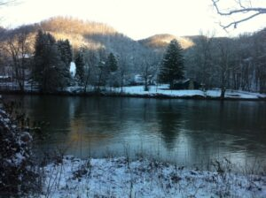 a snowy scene of camp from across the river
